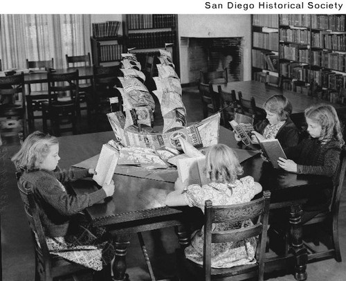 Children sitting at a table reading books in a San Diego State College library