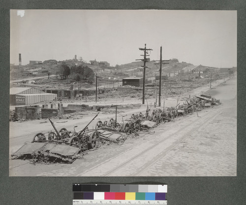[Row of cable cars destroyed by fire, Pacific Ave. at Polk St. Russian Hill in background.]