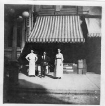 View next door to Pioneer Hall at 1007 7th Street. View shows Mr. and Mrs. Miller in front of their business