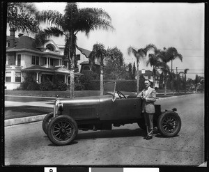 Man in a suit standing next to an open-air automobile, ca.1920