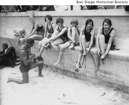 Women in bathing suits putting on roller skates, one receiving assistance from a man in a bathing suit