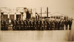 Large group of Japanese businessmen at a reunion of people from Mumamoto, Kaigaikyokai, Japan, standing in front of the original Sebastopol Chamber of Commerce mission-revival style building, about 1930