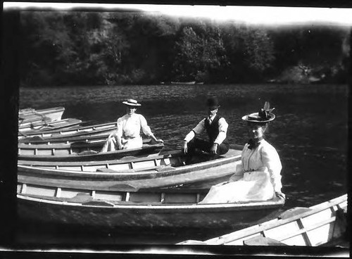 Three people in three separate boats--2 women and 1 man--among other empty boats apparently tied up to shore on the Russian River, circa 1900