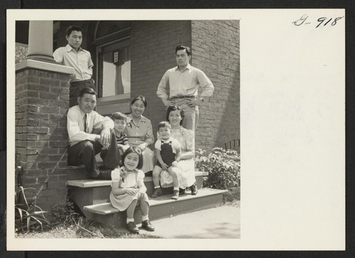 The Abe family from Colorado River, formerly of Seal Beach, California, gather on the porch of their new home to