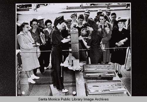 "Two Douglas employees demonstrate using tools to a group of women at the Douglas Aircraft Company plant ""Opportunity Day"" during World War II"