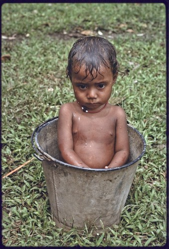 Young child bathes in a bucket of water