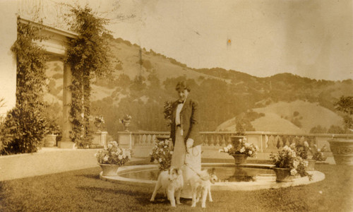 Alice Oge, and dogs, on the east side of the Beale house in San Rafael, California, September 1913 [photograph]
