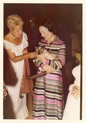 Mrs. Alice Tyler holding a Siamese cat and talking with a guest who is petting the cat (Color)
