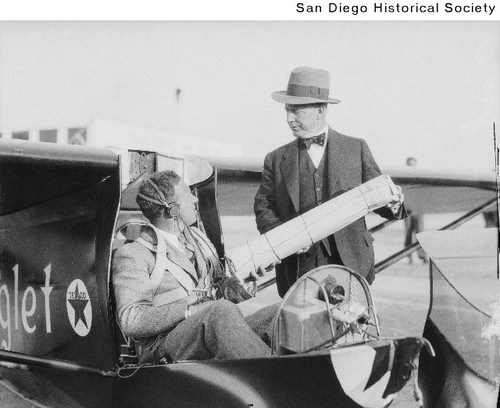 Frank M. Hawks seated in the glider Eaglet speaking with an unidentified man