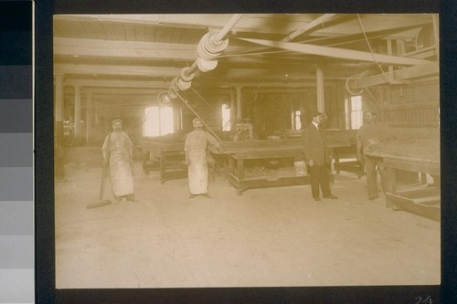 [Factory workers at cocoa tables.]