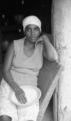 Woman sitting in a chair with a bowl of rice, San Basilio de Palenque, 1976