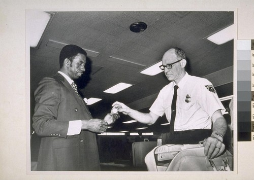 """Peking Ping Pong"". U.S. Customs inspector Louis Lazear (right) checks souvenir George H. Brathwaite brought back from Red China matches, insidious commie ping-pong ball, San Francisco Airport"