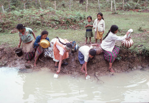 Guatemalan refugees collect water at a river, Santiago el Vértice, 1983