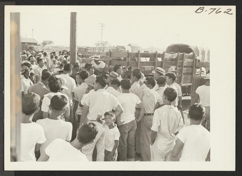 Showing a part of the crowd assembled to see the Gripsholm voyageurs off and the baggage trucks which carried their effects to Rivers, thence to an eastern seaport where they embarked Sept. 1, 1943. Photographer: Brown, Pauline Bates Poston, Arizona