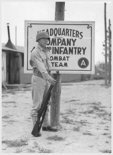 Private Noyama of Headquarters Company, 442nd combat team, stands guard at the entrance to Field Headquarters. The combat team wears