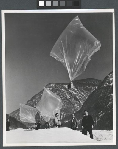 Photograph of balloons being released in front of mountains