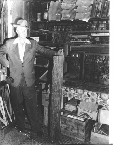 Unidentified man standing in front of shelves of artifacts, Petaluma, California, about 1970
