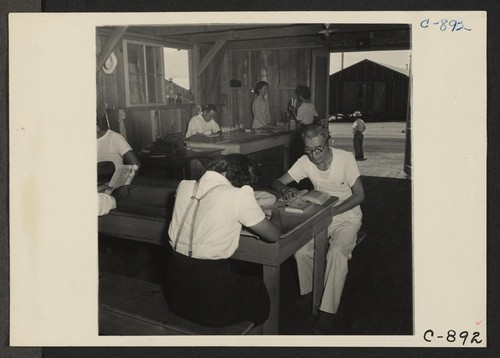 Manzanar, Calif.--One of the barrack buildings houses the library for evacuees at this War Relocation Authority center. The Librarian is a college graduate of Japanese ancestry who employs modern methods in library procedure. Photographer: Lange, Dorothea Manzanar, California