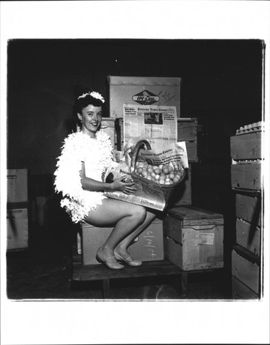 Betsy Olmsted Ashman with basket of eggs and an issue of the Argus Courier, Petaluma, California, 1955