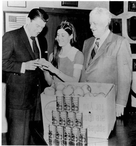"California Governor Ronald Reagan in the governor's office in Sacramento 1968 being presented with cases of apples, apple juice and apple sauce from ""Sebastopol's Finest"" by Sebastopol's Apple Queen with State Senator Randolph Collier looking on"