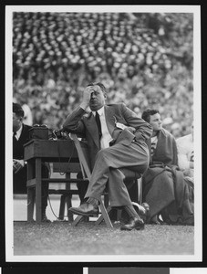 University of Southern California head football coach Jeff Cravath at the UCLA-USC game, sitting in a wooden chair on the sidelines rubbing his forehead, Los Angeles Coliseum, 1944