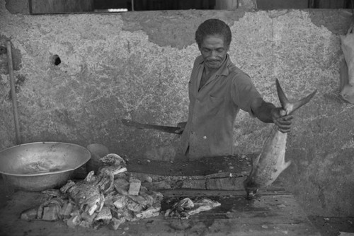 Man cleaning fish at city market, Cartagena Province, ca. 1978
