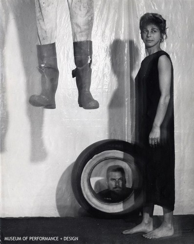 Anna Halprin standing with another male performer below looking through a tire