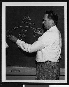 University of Southern California football coach Jeff Cravath diagramming a football play on a chalkboard, Los Angeles, 1949