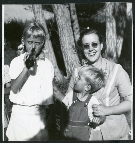 Photograph of three people, including two children, at a Manzanar hospital staff picnic
