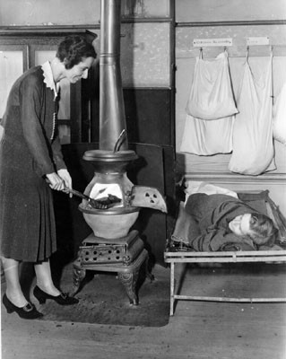 [Buena Vista School teacher Mary Brady shoveling coal into a stove while a student watches]