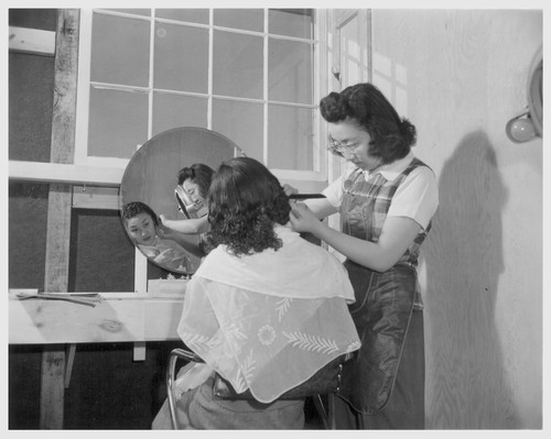 With makeshift equipment and arrangements, the cooperative beauty salon does a rushing business. Photographer: Parker, Tom Amache, Colorado