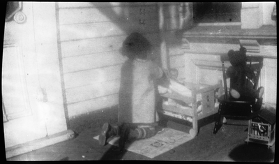 Gloria Pearl Roberts [?] playing with doll on front porch