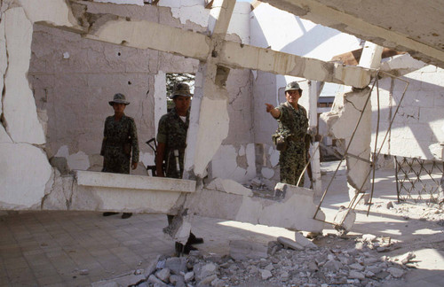 Soldiers stand near destroyed building, Guatemala, 1982