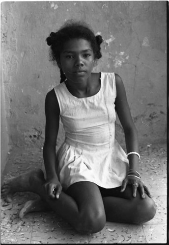 Girl sits outdoor on the floor, San Basilio de Palenque, 1975