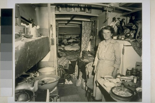 "Interior view of outmoded bus, now home for a family of six. This shipyard worker's wife wants ""a kitchen"""