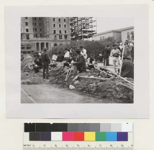 [Workers on break during street cleaning. Along Geary St. at Union Square. Hotel St. Francis in background.]