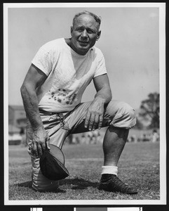 "University of Southern California assistant football coach Roy ""Bullet"" Baker, on one knee, white tshirt, holding cap in hand, Bovard Field, 1946"