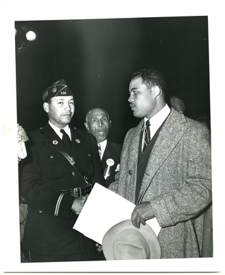 Joe Louis and unidentified man shaking hands, Frederick Roberts stands in the background