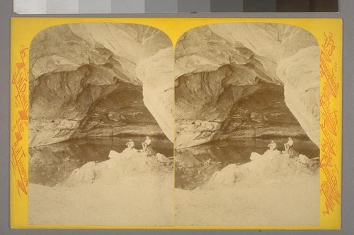 [Two men sitting on bank of river passing through overarching cavern]