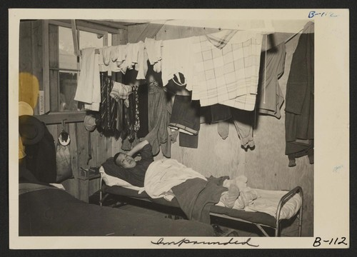 An evacuee resting on his cot after moving his belongings into this bare barracks room. Army cot and mattress are the only things furnished by the government. All personal belongings were brought by the evacuees. Photographer: Albers, Clem Manzanar, California