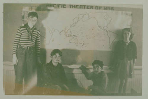 "Children from Canyon School (in Santa Monica Canyon) with map of the ""Pacific Theater of War"" displayed in a classroom during World War II"