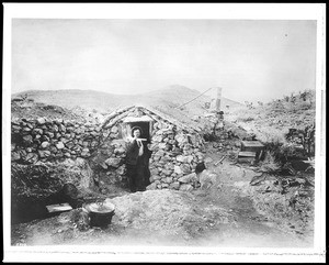 A desert miner standing in front of his stone cabin, near Randsburg, Kern County, California, ca.1900-1920