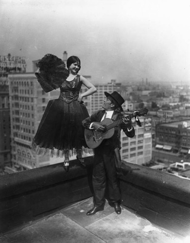 Dancer with fan on rooftop, view 3