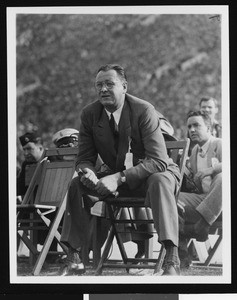 University of Southern California head football coach Jeff Cravath at the UCLA-USC game, sitting in a wooden chair on the sidelines holding a rolled up program, Los Angeles Coliseum, 1944