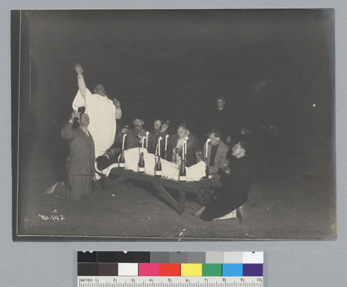 Night scene of men toasting to man on bench in mock wake, Bohemian Grove. [photographic print]