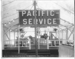"1912 Gravenstein Apple Show display by Pacific Gas & Electric Co., with a large electric sign ""Pacific Service"" and a display of an ""open"" house with various electric lights and appliances on display"