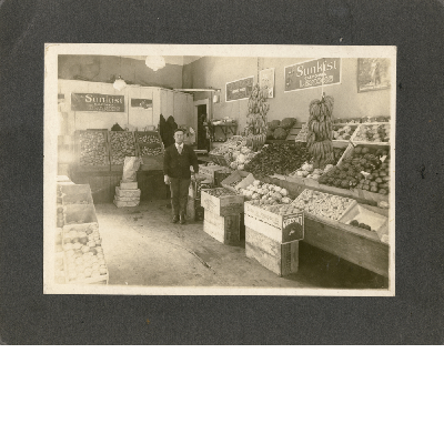 Unidentified produce merchant stands in his store in Oakland, California.