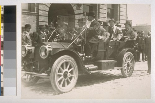 [Unidentified men in car, outside of court house.]