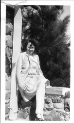 Bunni Cornelia E. Myers seated on a stone wall with pine trees in the background
