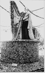 1914 Gravenstein Apple Show display or a round apple covered pedestal with harp made of apples being played by King Gravenstein mannequin dressed in cape made of apple slices
